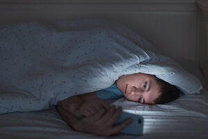 Sleepy depressed teenager surfing in the internet on his mobile phone lying on bed