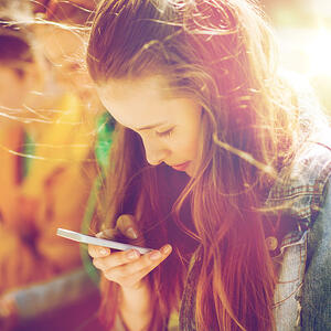 happy-teenage-friends-with-smartphones-outdoors-PV5AME3
